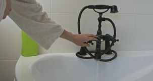 Hot water for bath. Woman put a water to bathtube from old fashion faucet. She wants to take bath stock footage