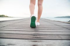 Woman put on white canvas shoes Royalty Free Stock Images