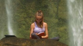 Woman Puts Aside Notebook Takes Red Book on Stone. Beautiful blond woman sitting on stone puts aside notebook and takes red paper book against waterfall stock footage