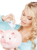 Woman puts cash money into big piggy bank. Buisness, banking and savings concept - happy businesswoman puts cash money into big piggy bank Royalty Free Stock Photo
