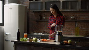 Woman puts chopped food ingredients into blender stock video footage