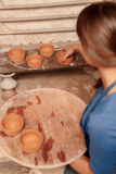 Woman puts clay pots on the shelf Royalty Free Stock Photos