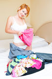 Woman puts clothes in suitcase. Stock Image