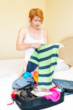 Woman puts clothes in suitcase. Stock Images