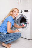 Woman puts clothes in the washing machine Royalty Free Stock Images
