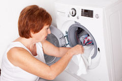 Woman puts clothes in the washing machine Royalty Free Stock Image