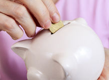 Woman puts a coin to the piggy bank Royalty Free Stock Photo