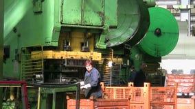 Woman puts component under press machine AutoVAZ factory. TOGLIATTI - SEP 30: Woman puts component under press machine AutoVAZ factory on September 30, 2011 in stock video