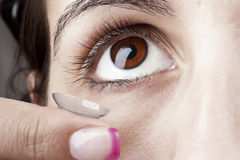 Woman puts on a Contact Lens. Woman applying a Contact Lens on her eye Stock Image