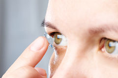 Woman puts contact lens Royalty Free Stock Photography