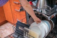 Woman puts dirty dish into dishwasher machine Stock Photography