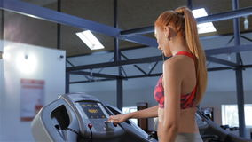 Woman puts earphones in her ears on treadmill at the fitness centre. Close up of young caucasian woman putting earphones in her ears on treadmill at the fitness stock video footage