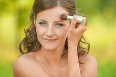 Woman puts on face powder brush Stock Image