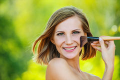 Woman puts on face powder brush Royalty Free Stock Photo