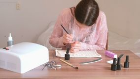 Woman puts first coat of pink shellac on her nails with small tassel. stock footage