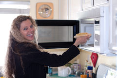Woman puts food in oven Stock Photos