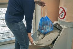 Woman puts a garbage bag in a lid of home garbage chute. In Moscow dwelling house Stock Photo
