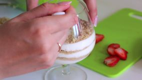 A woman puts in a glass layers ingredients for making dessert. Biscuit crumbs and cream. Nearby is a strawberry.