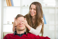 Woman puts his hand over his eyes a man to make him a surprise Stock Photography