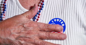 Woman Puts I Voted Sticker on Blouse. An elderly woman puts an I Voted sticker on her shirt stock footage