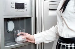 Woman puts ice cubes into the glass. Refrigerator is making fresh clean ice cubes Royalty Free Stock Photo