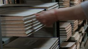 A woman puts a large book or newspaper set on a bookshelf in a library. Hand of a librarian close up. Back to school. Training and. A woman puts a large book or stock footage