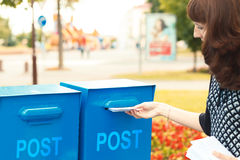 A woman puts letters in the mailbox Royalty Free Stock Images