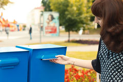 Woman puts letters in the mailbox Stock Images