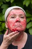 Woman puts a mask on the face of gooseberry Stock Photography