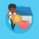 Woman puts money into piggy bank for buying house. Stock Photo