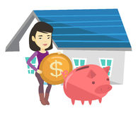 Woman puts money into piggy bank for buying house. Royalty Free Stock Images