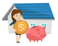 Woman puts money into piggy bank for buying house. Stock Photos