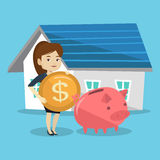 Woman puts money into piggy bank for buying house. Royalty Free Stock Photos