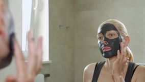 The woman puts a mud mask on a face. Face care. Mud Spa procedures. Day Spa. Drawing a black mask on the person