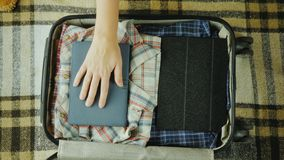 Woman puts a notebook in a travel suitcase.  royalty free stock images