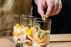 A woman puts a piece of kiwi in a glass of fruit for a fruit cocktail. Close-up,. Horizontal frame Stock Image