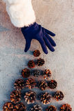 Woman puts Pinecone on top of Christmas decorated tree Stock Photography