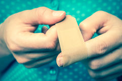 Woman puts a plaster on her injured finger - retro style Stock Image