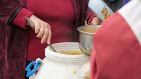 Woman puts porridge for homeless. Woman puts porridge in the pot for the homeless stock footage