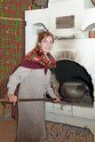 Woman puts a pot into russian stove Stock Photo