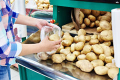 Woman puts potatoes in package Stock Photography