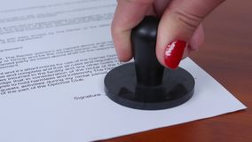Woman puts a round stamp on the document. Close up. People picks up the seal and seals the document, young woman takes and stamps the document, girl assured stock video footage