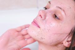 Woman puts a scrub on the face lying in the bathroom. Face close-up. White background. royalty free stock photos
