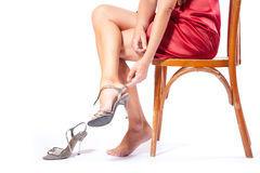 The woman puts shoes sitting on a chair royalty free stock images