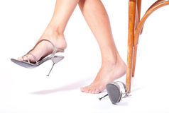The woman puts shoes sitting a chair Stock Photography