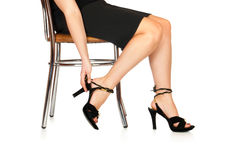The woman puts shoes sitting a chair Royalty Free Stock Image