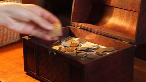 Woman Puts Silver Coin to Chest. Woman opens a antique value box and puts a silver coin, over the stacks of money stock video footage