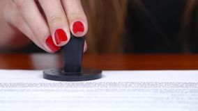 Woman puts a stamp on the document. Close up stock video
