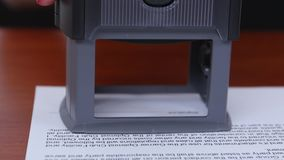 Woman puts a stamp on the document and denies in collaboration. Close up stock video footage