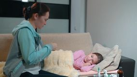 Woman puts a thermometer sick little daughter. Mother measures the temperature of her daughter`s body. stock footage